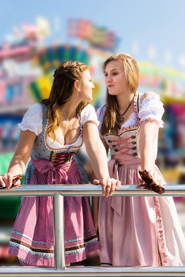 Attractive young women at German funfair Oktoberfest with traditional dirndl dresses royalty free stock photography