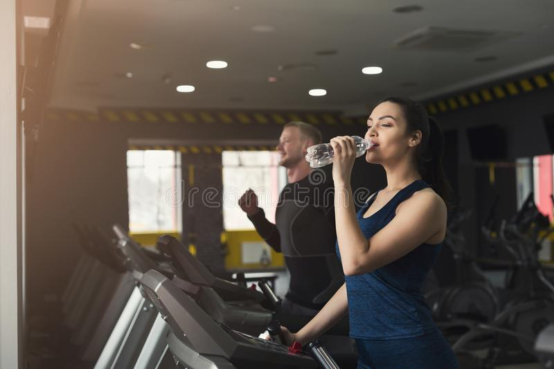 Attractive woman on treadmill in fitness club royalty free stock photo