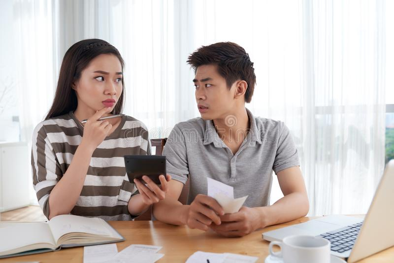 Unhappy Young Family Calculating Expenses royalty free stock photography