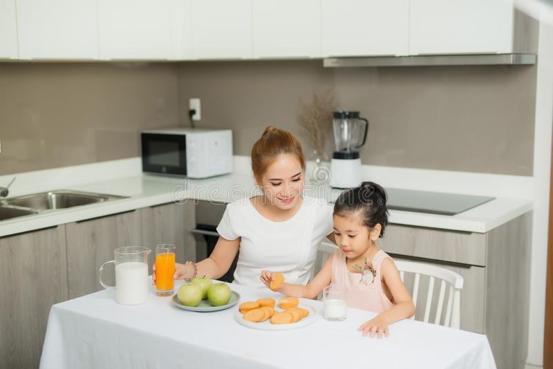 Attractive young woman and her little cute daughter are eating cakes and cookies on kitchen and drinking orange. Attractive young women and her little cute royalty free stock photos
