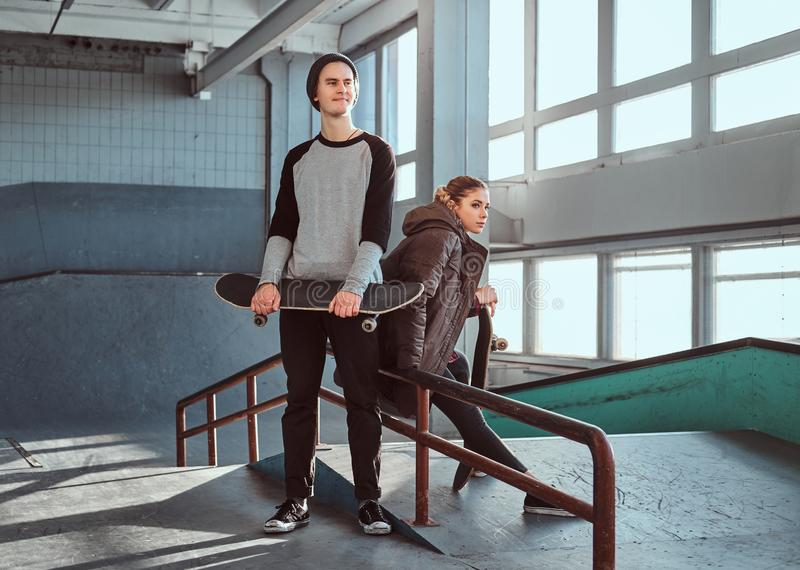 Attractive youth couple with skateboards next to a grind rail in skatepark indoors. stock photos