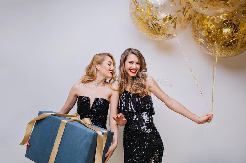 Attractive ypung women in black luxury dresses celebrating birthday party with big present and balloons on white. Background. Excited, having fun, charming royalty free stock images