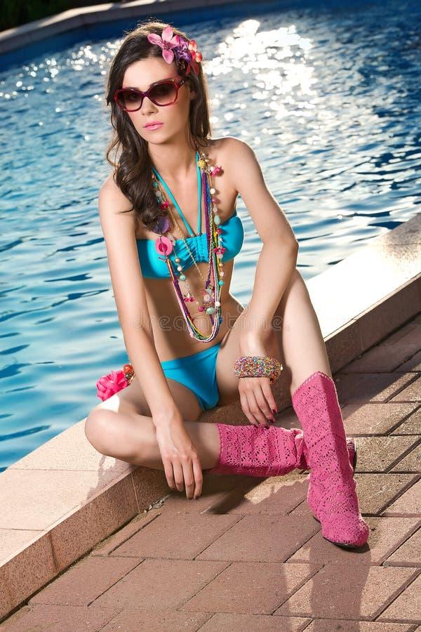 Attractivelvrouw het stellen door de pool royalty-vrije stock foto