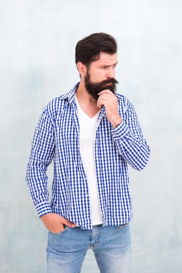 Attractiveness concept. Well groomed guy. Brutal handsome hipster man grey wall background. Bearded man trendy hipster royalty free stock photo