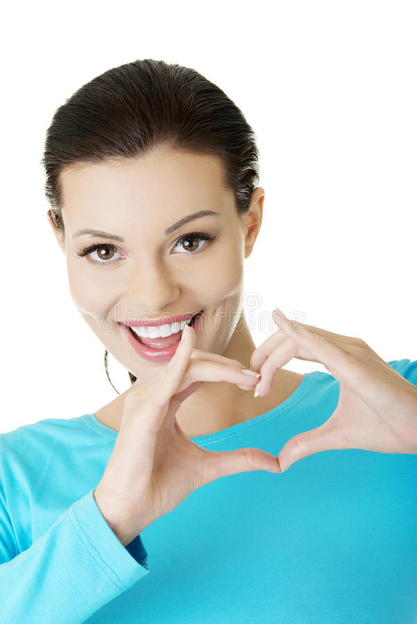 Attractiveyoung woman showing heart gesture. Attractive smiling young woman showing heart gesture with hands stock photos