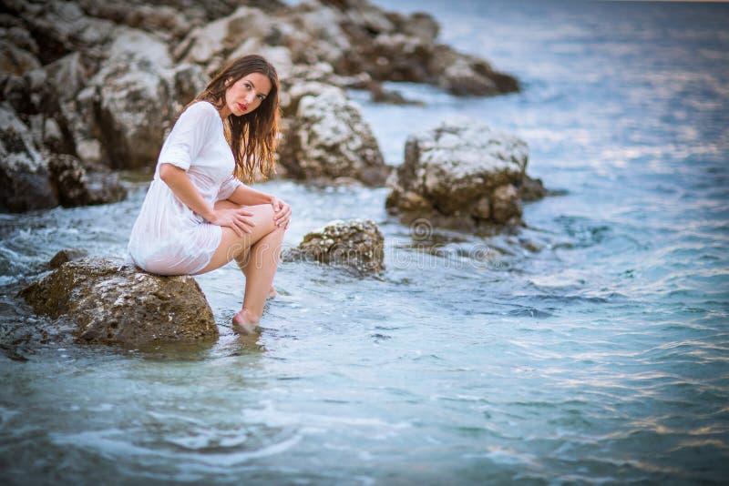 Attraente, giovane donna che si rilassa alla spiaggia immagini stock libere da diritti
