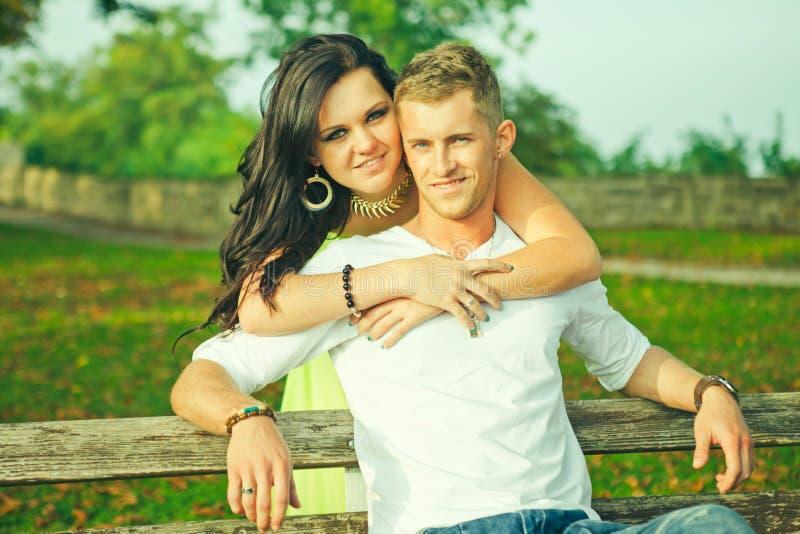 Attraente il tipo con la ragazza si siede ed abbraccia su un banco immagini stock