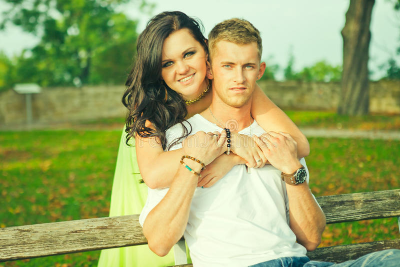 Attraente il tipo con la ragazza si siede ed abbraccia su un banco fotografie stock