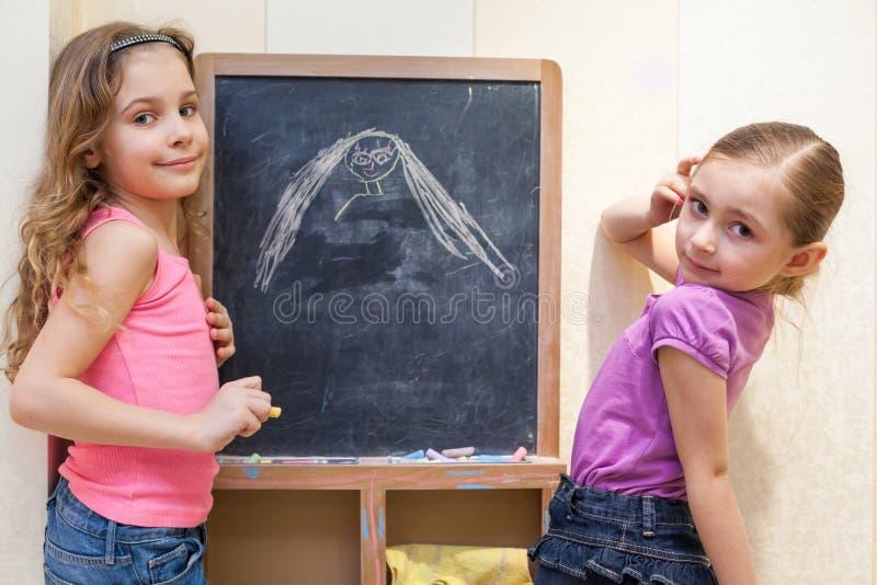 Attraktion för två små flickor med krita på svart tavla royaltyfri fotografi
