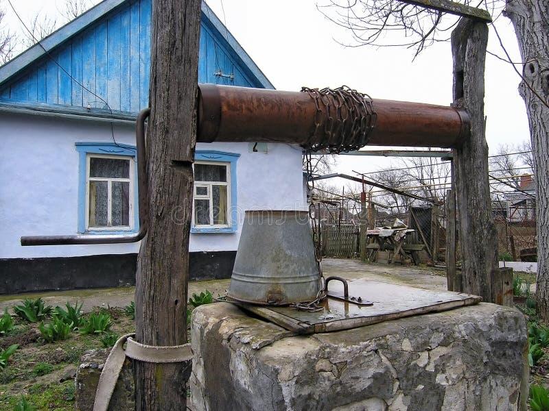 Attraktion väl med metallhinken på kedja som lantlig vattenförsörjning Autentiskt ryskt bygdliv Privata bönder hus och gård arkivfoto