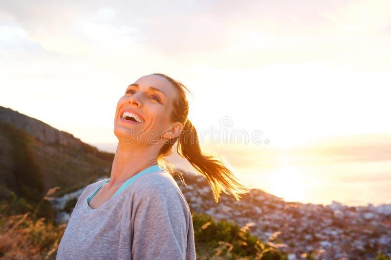 Attraktiv äldre kvinna som utomhus skrattar under solnedgång fotografering för bildbyråer
