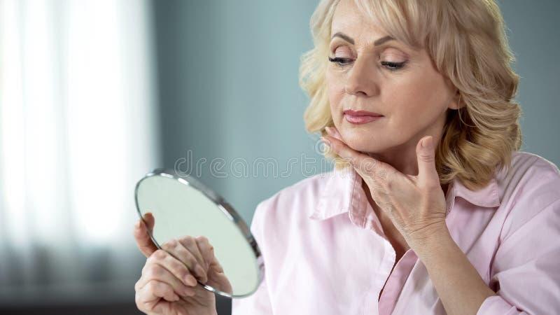 Attraktiv åldrig kvinna som ser hennes framsida i spegeln, plastikkirurgieffekt royaltyfri fotografi