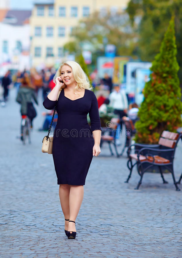 Attraktiv överviktig kvinna som talar på telefonen arkivfoton