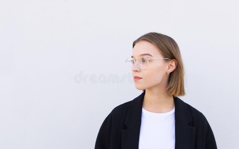 Attraktiv affärskvinna i ett omslag och exponeringsglasblickar på copyspacesidan som isoleras på en vit bakgrund royaltyfria bilder