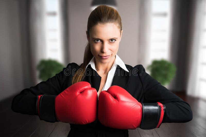 Attraktiv affärskvinna med boxninghandskar som är klara för en kamp royaltyfri foto