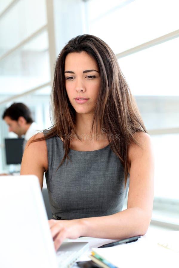 Attraktiv affärskvinna som arbetar på bärbara datorn royaltyfria bilder