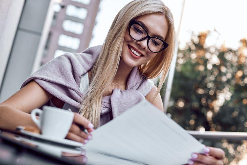 Attraktiv affärskvinna som läser tidningar på stadskafét arkivfoton