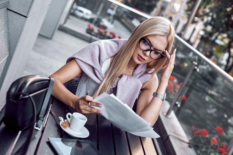 Attraktiv affärskvinna som läser tidningar på stadskafét royaltyfria bilder