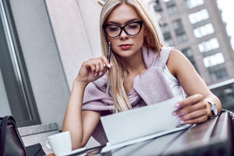 Attraktiv affärskvinna som läser tidningar på stadskafét arkivbilder
