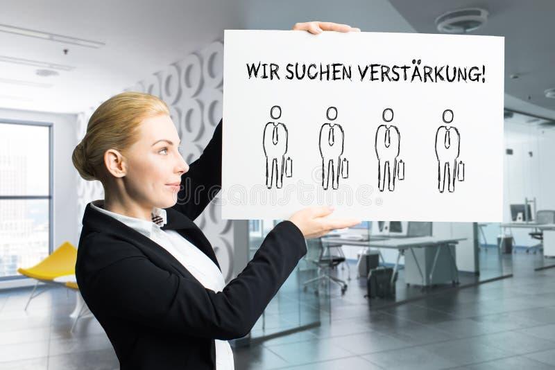 Attraktiv affärskvinna som rymmer ett tecken med meddelandet, 'som vi hyr 'i tyskt royaltyfria foton