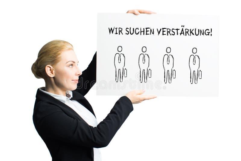 Attraktiv affärskvinna som rymmer ett tecken med meddelandet, 'som vi hyr 'i tyskt fotografering för bildbyråer