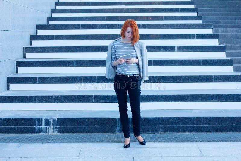 Attraktiv affärskvinna som ser på minnestavlan på bakgrunden av trappan i affärsmitten arkivfoto
