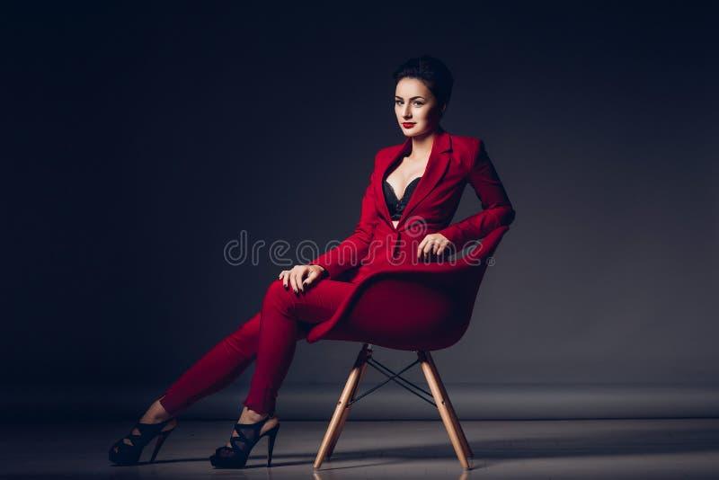 attraktiv affärskvinna Stående av en sexig ung affärsdam i en röd dräkt på en mörk bakgrund royaltyfri fotografi