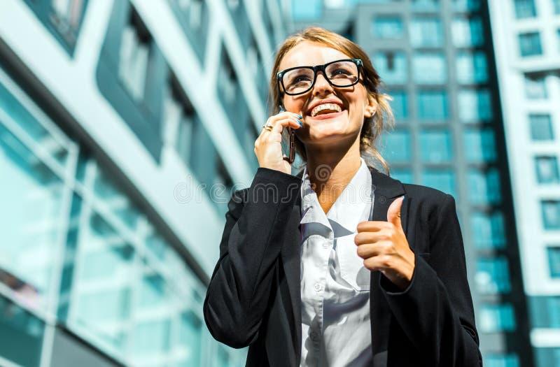 Attraktiv affärskvinna Talking vid telefonen med tummen upp fotografering för bildbyråer