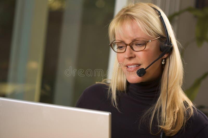 attraktiv affärskvinnahörlurar med mikrofontelefon royaltyfria foton
