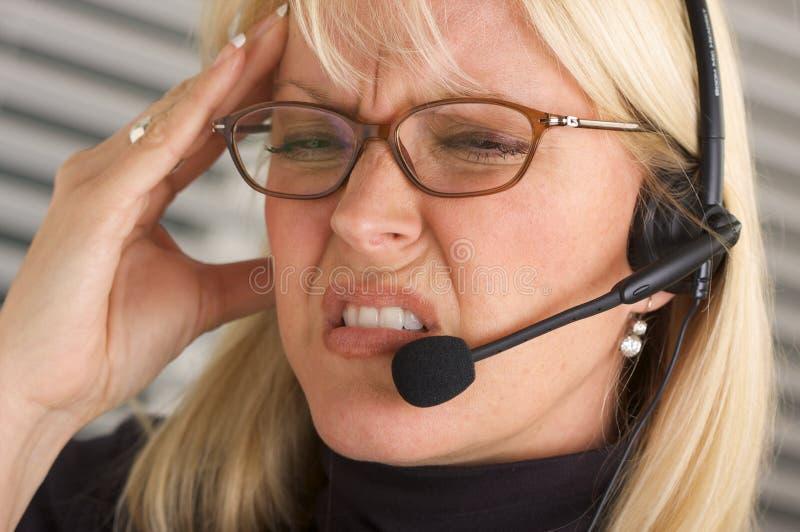 attraktiv affärskvinnahörlurar med mikrofontelefon fotografering för bildbyråer