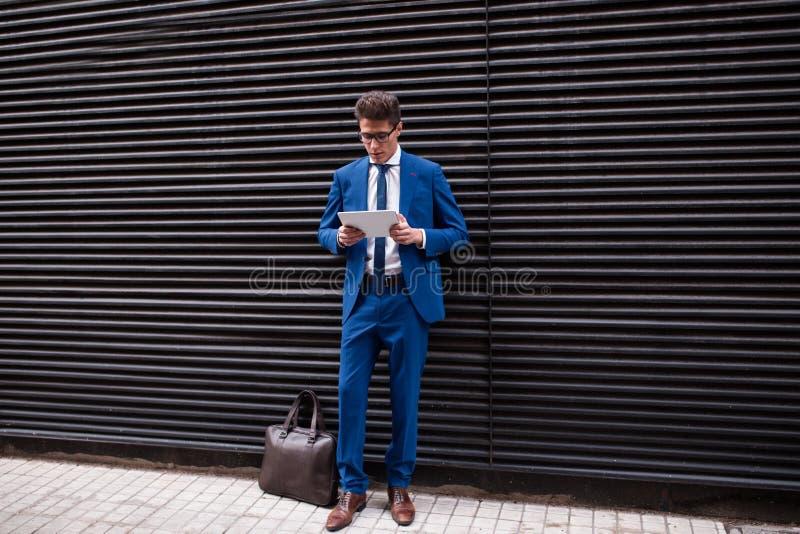 Attraktiv affärsman som använder en minnestavladator fotografering för bildbyråer