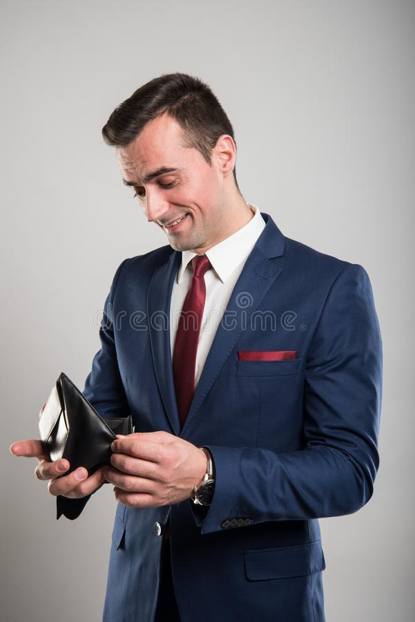 Attraktiv affärsman som ser i hans plånbok och le royaltyfri fotografi