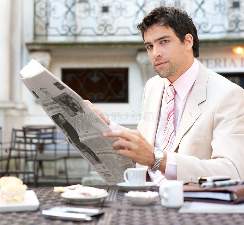 Attraktiv affärsmanläsning som är pappers- i cafe. royaltyfri fotografi