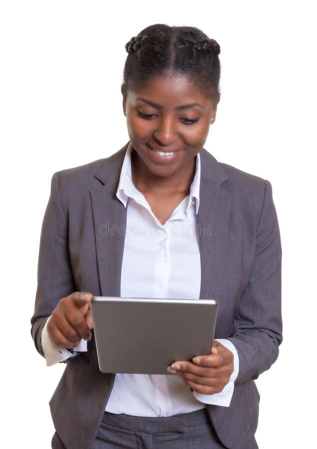 Attraktiv afrikansk affärskvinna som arbetar med minnestavladatoren fotografering för bildbyråer