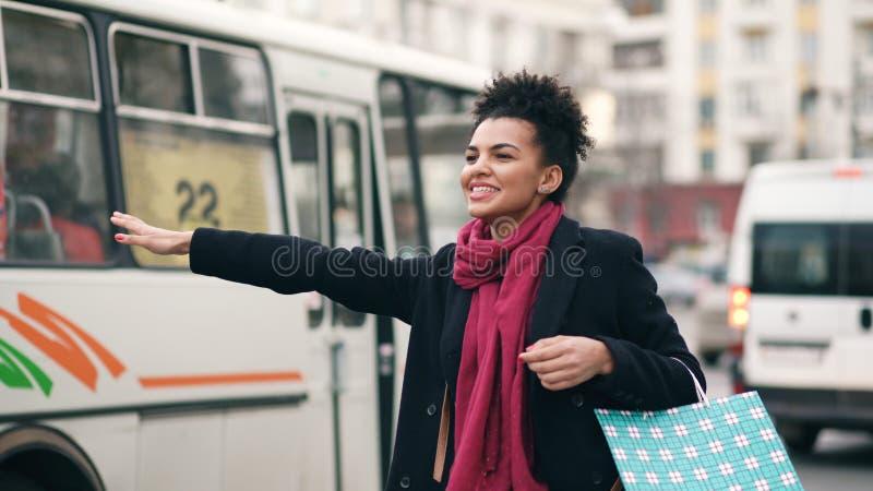 Attraktiv afrikansk amerikankvinna med shoppingpåsar som talar telefonen, medan vänta på taxitaxin och komma tillbaka från galler arkivbild