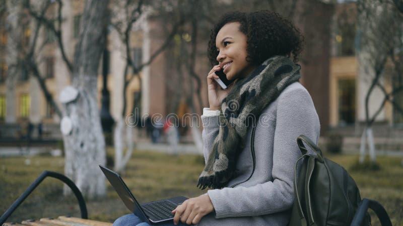 Attraktiv afrikansk amerikanstudentflicka som utomhus talar hennes telefonsammanträde på bänk med bärbar datordatoren arkivbild