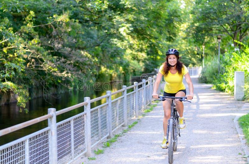 Attraktiv aktiv ung kvinna som rider en cykel arkivbild