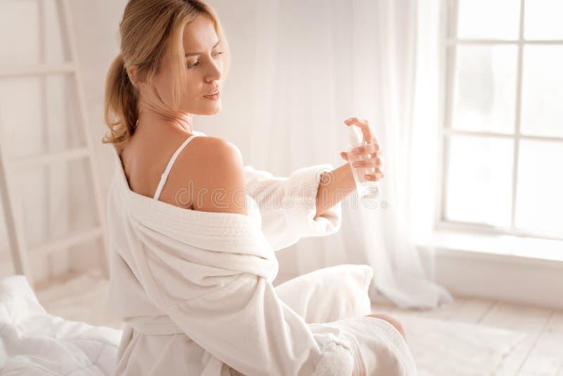 Attraktiv angenäm kvinna som använder kroppsprej royaltyfria foton