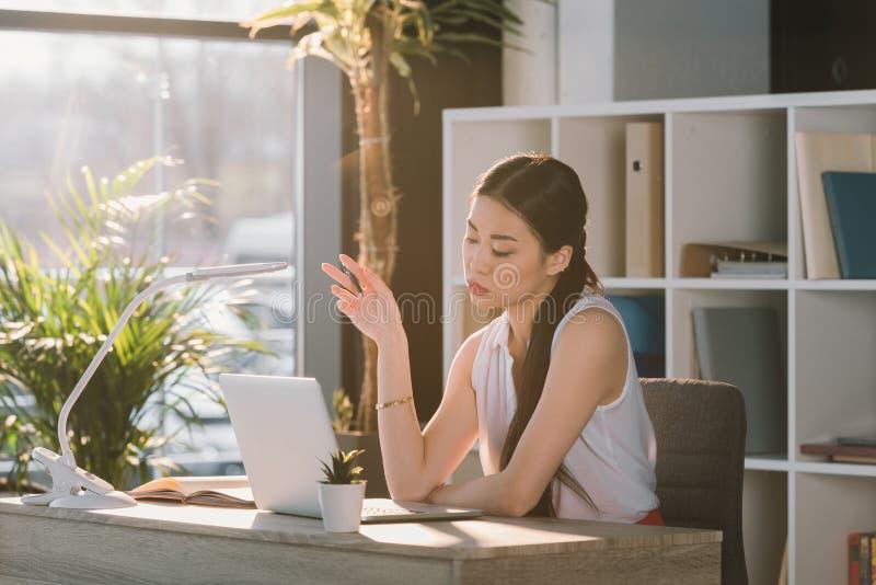 Attraktiv asiatisk affärskvinna med bärbara datorn som i regeringsställning tänker på arbetsplatsen fotografering för bildbyråer