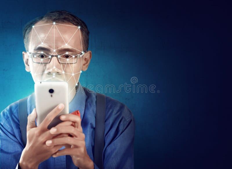 Attraktiv asiatisk affärsman med mobiltelefonen genom att använda framsidaerkännande royaltyfri bild