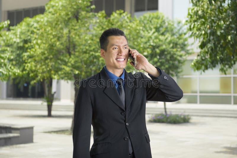 Attraktiv asiatisk affärsman som talar på hans telefon, medan stå fotografering för bildbyråer