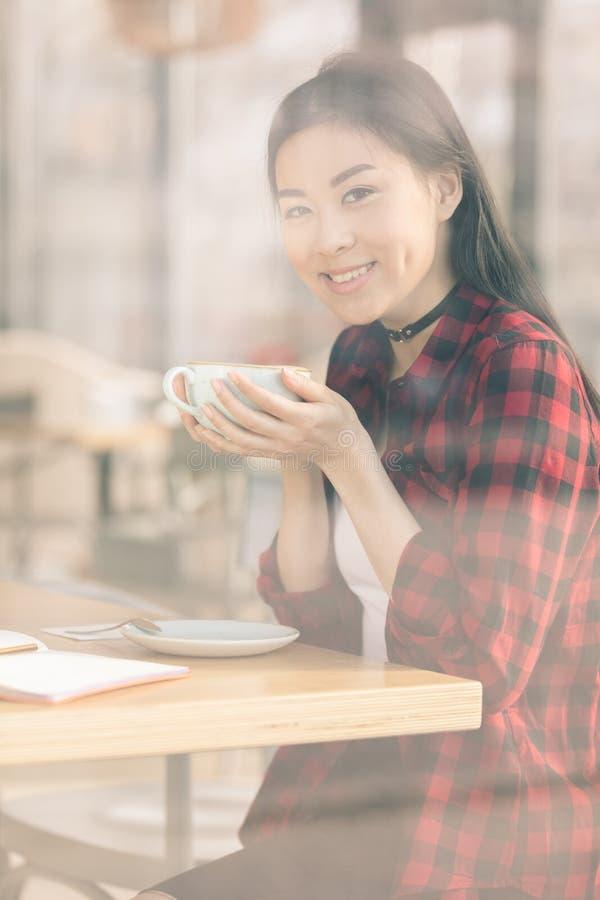 attraktiv asiatisk flicka som dricker kaffe i kafékaffe royaltyfri fotografi
