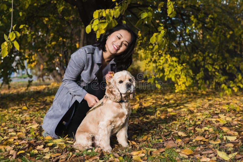 Attraktiv asiatisk kvinna med hunden i parkera arkivfoto