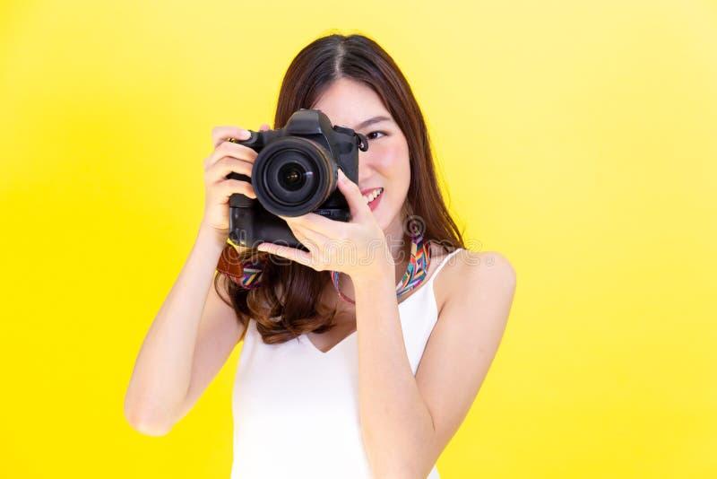 Attraktiv asiatisk kvinna som rymmer en yrkesmässig kamera och tar foto över gul bakgrund fotografering för bildbyråer