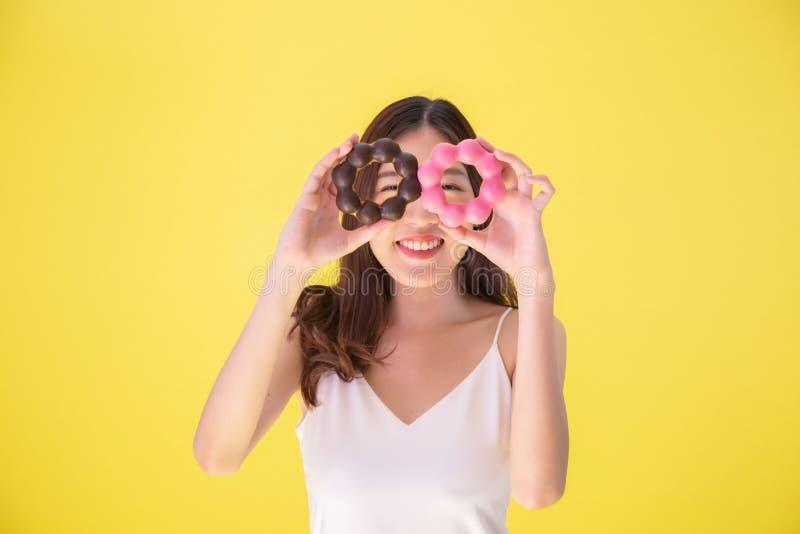 Attraktiv asiatisk kvinna som rymmer två donuts med gulligt le uttryck över gul bakgrund arkivbild