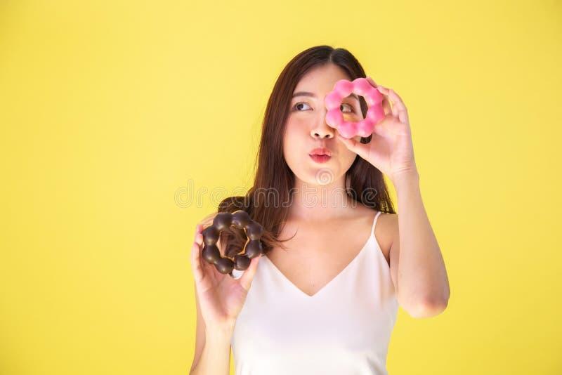 Attraktiv asiatisk kvinna som rymmer två donuts med gulligt uttryck över gul bakgrund royaltyfri foto