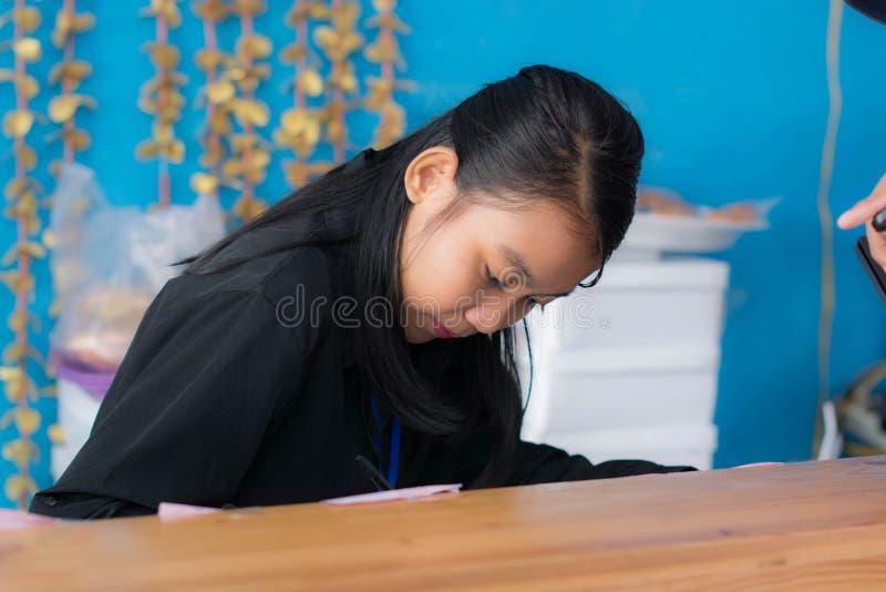 Attraktiv asiatisk kvinna som skriver genom att använda pennan bak skrivbordet arkivbilder