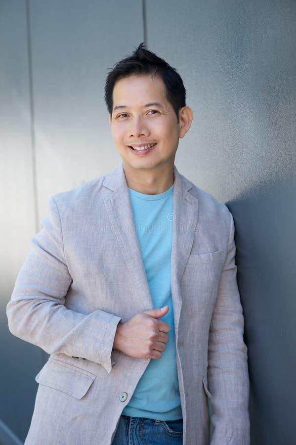 Attraktiv asiatisk man som utomhus ler royaltyfri bild