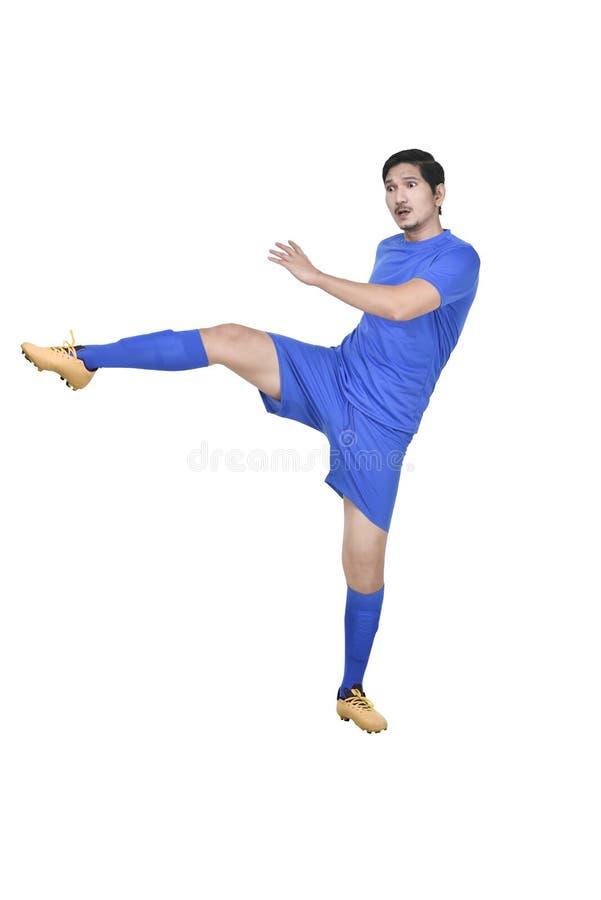 Attraktiv asiatisk manlig fotbollspelare som sparkar bollen royaltyfria foton