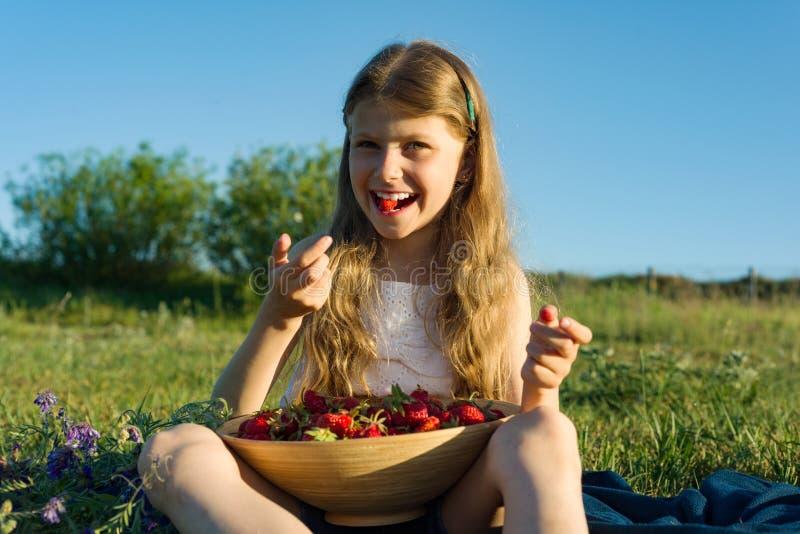 Attraktiv barnflicka som äter jordgubben Naturbakgrund, grön äng, landsstil royaltyfri bild